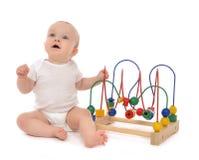 De babypeuter die van het zuigelingskind spelend houten onderwijs aan bevinden zich stock afbeelding