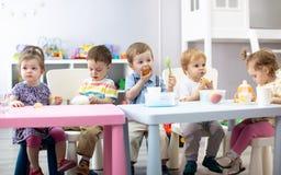 De babys hebben lunch in kinderdagverblijf stock afbeelding