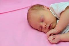 De babyslaap op het bed met pingelt achtergrond Stock Afbeelding