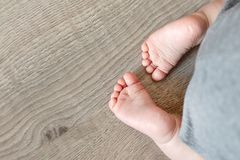 De babyvoeten van de close-up leuke zuigeling op houten vloerachtergrond Grappige aanbiddelijke hielen Tedere childsteen royalty-vrije stock afbeeldingen