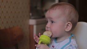 De babyzitting en eet thuis stock videobeelden
