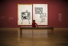 De babyzitting en ziet op beeld op Keith Haring-tentoonstelling in de galerij van Albertina royalty-vrije stock afbeelding