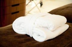 De badjas ligt op de rand van het bed in het hotel Stock Fotografie