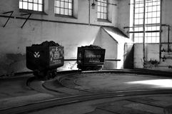 De baggermachine laadt de vrachtwagensteenkool stock afbeeldingen