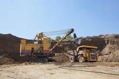 De baggermachine laadt de vrachtwagensteenkool De baggermachine laadt de vrachtwagengrond Stock Fotografie