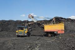 De baggermachine laadt de vrachtwagensteenkool De baggermachine laadt de vrachtwagensteenkool Royalty-vrije Stock Afbeeldingen