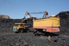 De baggermachine laadt de vrachtwagensteenkool De baggermachine laadt de vrachtwagensteenkool Stock Afbeelding