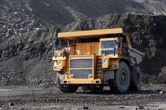 De baggermachine laadt de vrachtwagensteenkool De vrachtwagen die steenkool vervoert Stock Afbeeldingen
