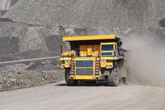 De baggermachine laadt de vrachtwagensteenkool De vrachtwagen die steenkool vervoert Stock Fotografie