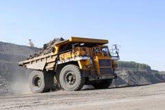 De baggermachine laadt de vrachtwagensteenkool De vrachtwagen die steenkool vervoert Royalty-vrije Stock Afbeeldingen