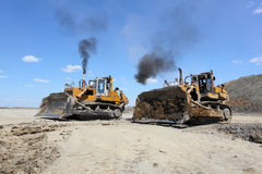 De baggermachine laadt de vrachtwagensteenkool Twee bulldozers Royalty-vrije Stock Afbeelding
