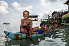 De Bajaukinderen ontspannen op een uitgegraven boot dichtbij oever in Sabah, Maleisië royalty-vrije stock afbeeldingen