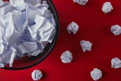 de bak van het bureauafval met verfrommelde documenten op rood tafelblad royalty-vrije stock afbeelding