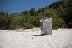 De bak van het huisvuil op een strand Stock Afbeeldingen