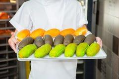 De bakker houdt verse multicolored broodjes op de achtergrond van de oven stock foto's