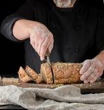 de bakker snijdt een mes in plakken van roggebrood met pompoenzaden stock foto's