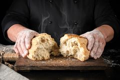 de bakker in zwarte eenvormig brak in de helft van een geheel gebakken brood van wit tarwemeelbrood royalty-vrije stock fotografie