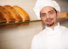 De bakkerijeigenaar kleedde zich in de kledij van de chef-kok Stock Fotografie