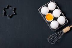 De bakselachtergrond met eieren, zwaait en speelt de snijders van het vormkoekje mee Stock Foto