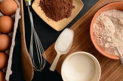 De bakselingrediënten op een steen dienen in: eieren, bloem, suiker en cacao Royalty-vrije Stock Foto's