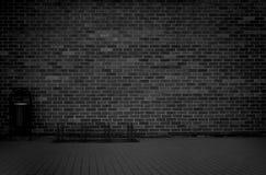 De baksteen grunge doorstond zwarte muurachtergrond met gang en vuilnisbak stock afbeeldingen