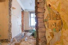 De bakstenen muur met oude paperhangings is het deel van binnenland van flat tijdens op de vernieuwing stock afbeelding