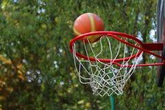 De bal bij basketbalhoepel die wordt geworpen Stock Afbeeldingen