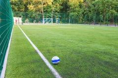 De bal ligt op het groene gras van de nieuwe voetbal & x28; soccer& x29; gebied royalty-vrije stock foto