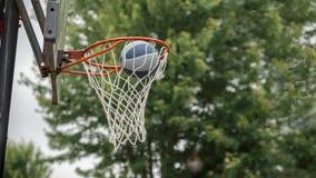 De bal valt in de basketbalhoepel in park stock afbeelding