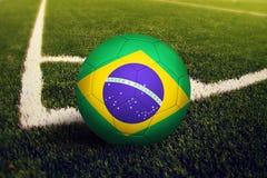 De bal van Brazili? op de positie van de hoekschop, de achtergrond van het voetbalgebied Nationaal voetbalthema op groen gras royalty-vrije stock foto's