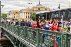 De bal van de deelnemers van het Nationaliteitenfestival gaat tot het punt van de prestaties over de Dvortsoviy-brug over Stock Foto