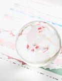 De bal van de glasaarde op de financiële grafiek Stock Foto's
