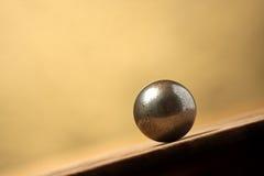 De bal van het metaal op het hellen oppervlakte Stock Afbeelding