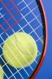 De bal van het tennis is onder een deel van een tennisracket Royalty-vrije Stock Afbeeldingen