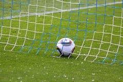 De bal van het voetbal binnen het net Stock Foto's