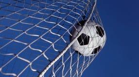 De bal van het voetbal die in een doel wordt geschopt stock fotografie