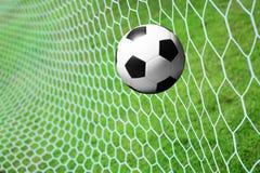 De bal van het voetbal in netto doel stock afbeelding