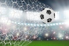 De bal van het voetbal in netto doel stock afbeeldingen