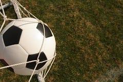 De bal van het voetbal in netto doel Stock Foto's