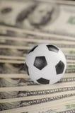 De bal van het voetbal op achtergrond van dollars Royalty-vrije Stock Foto