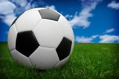 De bal van het voetbal op gras stock afbeeldingen