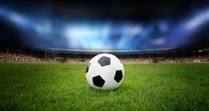 De bal van het voetbal op het gebied stock afbeelding