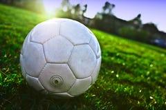 De bal van het voetbal op het gras stock afbeeldingen