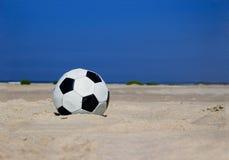 De bal van het voetbal op zandig strand stock fotografie