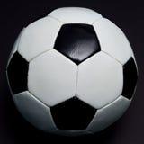 De bal van het voetbal op zwarte Stock Afbeeldingen