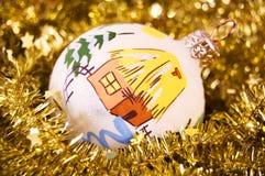 De bal van Kerstmis in een gouden slinger met sterren Stock Afbeeldingen