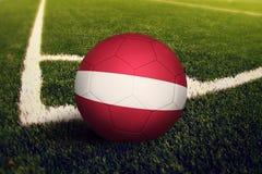 De bal van Letland op de positie van de hoekschop, de achtergrond van het voetbalgebied Nationaal voetbalthema op groen gras stock foto's
