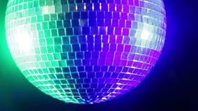 De bal van de spiegeldisco op een zwarte achtergrond in het licht van blauwe en groene schijnwerpers stock footage
