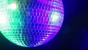 De bal van de spiegeldisco op een zwarte achtergrond in het licht van blauwe en groene schijnwerpers stock video