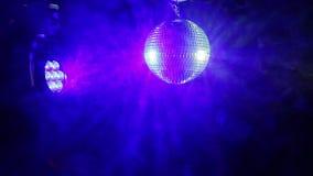 De bal van de spiegeldisco op een zwarte achtergrond met schijnwerpers leidde bij hem van verschillende kleuren in de rook stock video